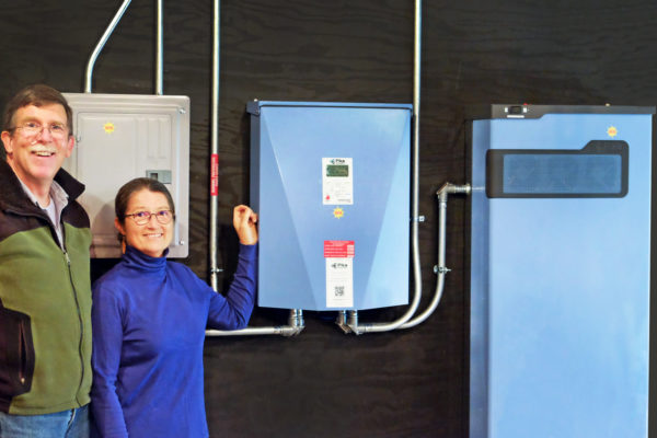 Two homeowners stand by their home battery backup power source, a Maine-made battery charged with solar power