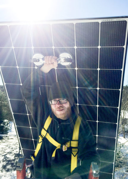 solar installer in maine carries a solar panel to the roof in winter