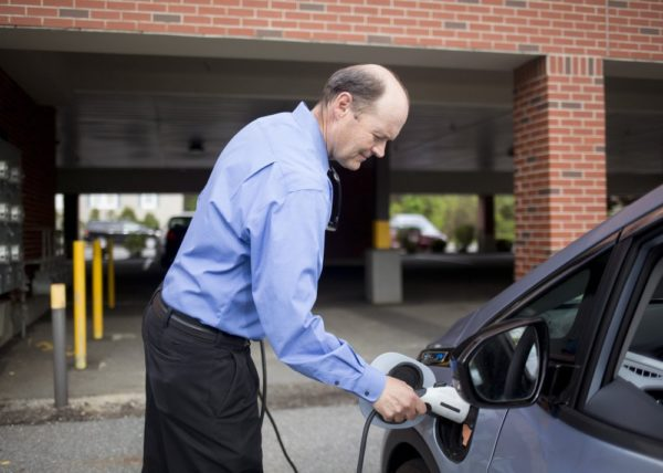 Barry Woods plugs in an electric car in Portland, Maine. Photo Courtesy Portland Press Herald.
