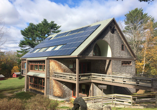 A grid-tied solar electric system (with solar hot water, top middle) installed in Maine.
