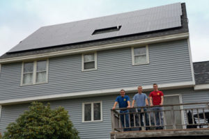 Ian Gershuny (far left), with sons Josh and Kyle, in front of their new solar PV array! The system will immediately save their household ~$4,000 in electricity annually, enough to neutralize payments on a solar loan. When the solar loan is paid off, they'll be earning money from sunshine.