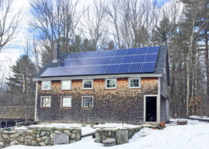 home with solar panels in snowy winter