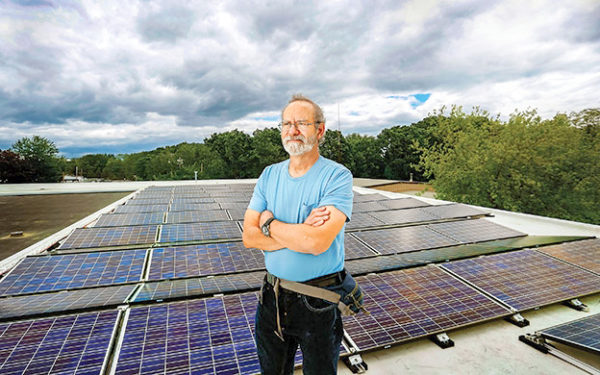 Barry with Caravan's largest solar array. Photo courtesy Tim Greenway for Mainebiz.