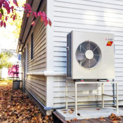Exterior heat pump unit installed on a metal base with sound dampening hardware