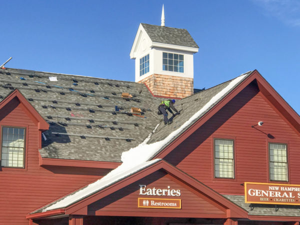 A ReVision Energy installer installs racking on the roof of the Common Man Roadside in Hooksett, NH