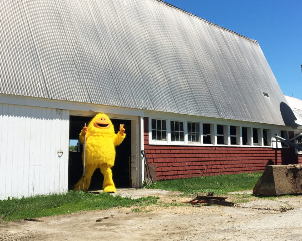 Sunsquatch stands in the doorway of a barn with a garden fork
