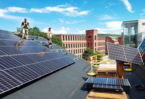 Installers place panels on a rooftop array for Claremont MakerSpace in NH